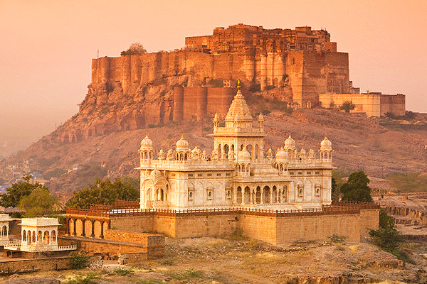 A golden image of a white detailed temple in the foreground and huge, golden, olden temple on the top of a hill behind it - Osian / Rajasthan